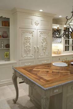 french country kitchen, fabulous cabinets and I do believe that is the refridgerator hidden behind thoses gorgeous panels... Love the details