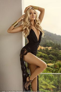 Lacy lady: The star dazzled in a plunging black swimsuit with a lace overlay as she posed seductively alongside the villa wall, popping her hip and running her fingers through her bouncy looks