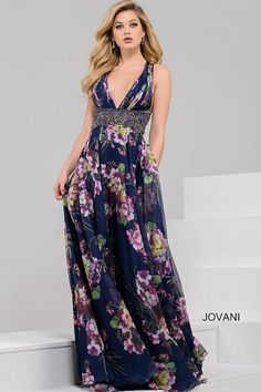 Beautiful floor length navy chiffon dress with multi color floral print features sleeveless bodice with plunging neckline and open back and embellished belt.