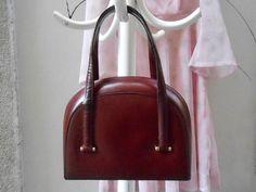 Rara borsa di Gucci dei primi anni 60 con doppio manico corto da portare a mano. Gli interni, in pelle rossa, presentano tre scomparti di cui uno