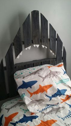 DIY shark pallet headboard The headboard is a free pallet I had. I cut it down with a saws all. I sanded all the edges. Gave it a wash of color. I cut the mouth the way I did to have a shelf above his head. The teeth are from one of the kid's foam material placemats. No risk of pointy sharp wood teeth. I cut the teeth and glued them on.