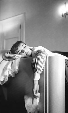 A 24 year old Audrey Hepburn exhausted from a long day at Paramount Studios, lays down in her Los Angeles hotel room clutching a letter from home. Photograph by Bob Willoughby (1953).