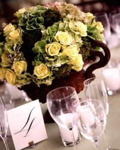 Rustic Centerpiece  A painterly mix of green hydrangea, jade roses, and moss are arranged in cast-iron garden urns.