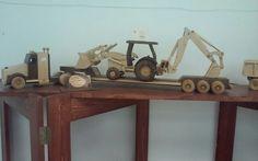 Wooden loader backhoe on tractor trailer rig