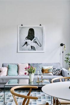 Sofá gris y tonos pastel en los cojines. Fotografía en la pared. Mesa de centro con candelabros dorados y flores.