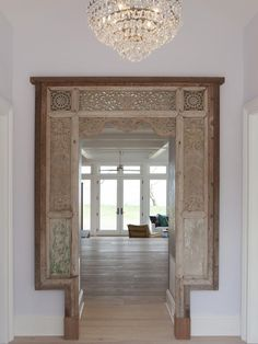 An intricate Brazilian doorway evokes a global, eclectic vibe as soon as guests enter the foyer, setting the tone for the rest of the home
