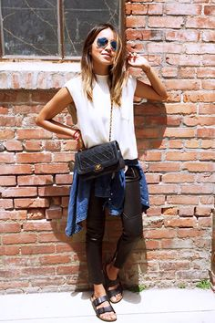 White sleeveless top tucked into black leather pants with zips and black Birkenstock sandals