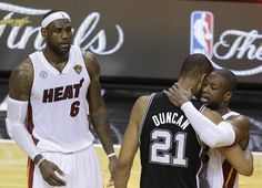 The San Antonio Spurs' Tim Duncan (21) embraces Miami Heat's Dwyane Wade (3) as Miami Heat's LeBron James (6) looks on after the second half in Game 7 of the NBA basketball
