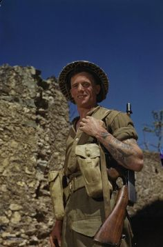 The 'Infantryman'. Corporal M Smith of the Duke of Cornwall's Light Infantry, with his rifle over his shoulder at the main Headquarters of the Eighth Army in the San Angelo area. Corporal Smith, a former metal polisher from Birmingham, served in North Africa and Egypt before going to Italy in early 1944. He was involved in the fighting north of Cassino and on the Garigliano River.