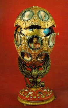 Romanov 300th Egg.The egg is held by a threefold heraldic eagle, symbolizing the power and glory of the Romanov Dynasty. The eagles are holding the Imperial scepter, orb and the Romanov sword in their talons. The purpurine base on which they stand represents the Russian Imperial shield.
