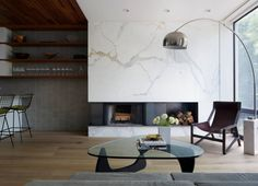 Glass coffee table in the large living room with the bent lamp and marble wall with built-in eco fireplace