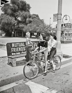 Two women ride a bicycle built for two during the Los Angeles bus strike of 1955.
