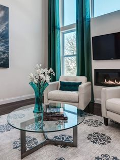Turquoise floor-to-ceiling drapes accentuate the tall ceiling and windows in this contemporary living room. A wall fireplace warms up and adds ambiance to the space.