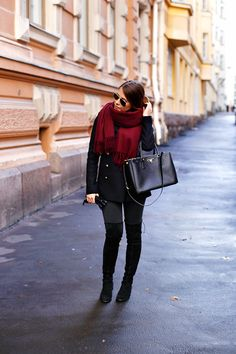 Marianna Mäkelä's crimson tasselled scarf goes a treat with her over the knee boots and jeans. Coat: Zara, Scarf: Acne, Jeans: Topshop, Boots: Stuart Weitzman, Bag: Prada.