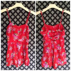 F21 red floral romper Bright red romper with adjustable spaghetti straps and floral print pattern. Has buttons on the chest and the shorts also have pockets. The back has a cut out cross cross design. Zips up on the side. Forever 21 Pants Jumpsuits & Rompers