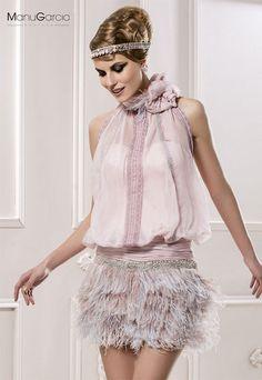 Vestido de gasa color nude de escote halter, detalle drapeado en la cadera de gasa con aplicación de pedrería, cuerpo ablusado con puntillas y espalda al aire, falda en plumas de avestruz en plata y nude