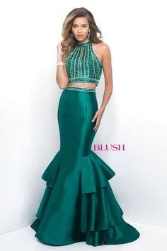 This red carpet worthy  two piece mermaid features a fully beaded bodice, high neck, and open back. The voluminous skirt has a finished hem and tiered court train. Back zipper closure.