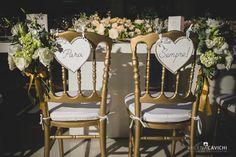Cadeira dos noivos Dior dourada com arranjo floral e plaquinha em formato de coração.