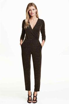 Glitterende jumpsuit: Een jumpsuit van tricot waarin glittergaren is verwerkt. Het model heeft lange mouwen, smal toelopende pijpen, een overslag bovenaan en een naad met elastiek in de taille. Haak-en-oogsluiting voor. Steekzakken.