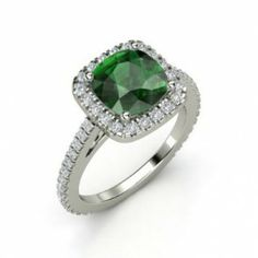 Cushion Cut Emerald & White Diamond Engagement Ring - If she has a thing for green then this would be the perfect ring with this 18k White Gold Cushion Cut Emerald & White Diamond Engagement Ring placed in a Prong setting featuring a Green Cushion cut center stone with White Round cut accent stones on the halo mount & shank. This Cushion Cut Emerald engagement ring is a VS-SI in clarity & a D-F in color. The total weight is 2.29 carats & the diamonds are 100% natural. #unusualengagementrings