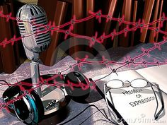A little radio station, with its microphone and headphones close to it, and a opened book with glasses on it. On the book we can read Freedom of expression. In the foreground of the image, barbed wire symbolizes   the ban of the freedom of expression.