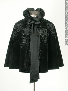 Black velvet cape with beautiful embellishments. 1895-1900 The McCord Museum. Passementerie, trimmings. Cloak.