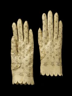 These gloves are typical of a style of glove produced in Spain about 1800. They are kidskin dyed in pastel colours and printed in black in decorative and figurative designs. This style of glove must have been a brief, but very popular fad of the last years of the 18th century. As gloves were one of the few gifts a man could give to a single woman he was not engaged to marry, new designs and colours were eagerly sought after to provide variety in this staple form of present.