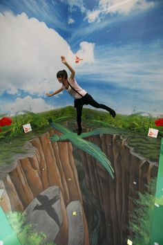 """A girl poses at a 3-D chalk drawing in an exhibition entitled """"The house of 3D Art Illusion"""" at a shopping center in Hong Kong Wednesday, July 14, 2010. The interactive exhibition is open to the public to enjoy the visual experience. (AP Photo/Kin Cheung)"""