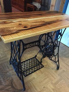 End table made from antique Singer sewing machine with rough sawed lumber used as top.