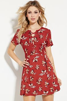 A short-sleeved woven dress featuring an allover floral print with a lace-up neckline and a mini length.
