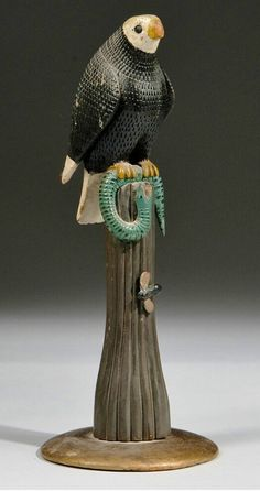 Skinner Auction: 2744M 8/10/14 Lot: 710.  Estimate $1,500-2,500.   Sold for: $2,337.  Description:  Carved and Painted Folk Art Figural Group, America, probably c. 1930. Bald eagle with chip-carved feathers grasps in its talons a green-painted snake with black spots, the eagle perched atop a reeded swelled column with a carved bee, on gold-painted circular base, original paint, eagle with wear to bill, and loss to one wing.  ht. 14, base dia. 5 1/2 in.