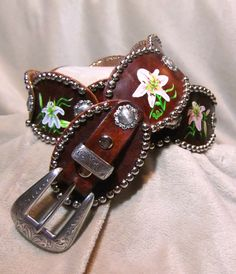 Lilly flowers on oval conchos with antique silver.