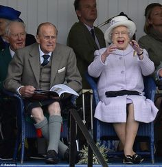 One is amused! Prince Philip and Queen Elizabeth cheer as competitors participate in a sack race at the Braemar Gathering in Scotland
