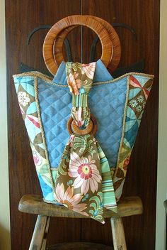 """""""L'Aqua Bag"""" sewn by Jeanine! Made with Amy's Ginger Bliss line of fabric. Machine quilted denim, with quilted piece work made from Amy's beautiful fabric. Jute piping around side, top and bottom of the bag, as well as piping in the inside two open pockets. An inside zippered pocket keeps personal belongings safe and secure. Rattan handles and decorative rattan accent loops polish it off. The tote bag closes with a magnetic hidden snap under the rattan accent piece. (sewn in-between the…"""