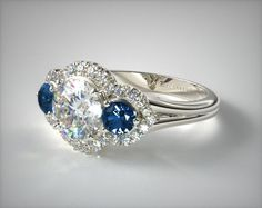 SKU 55360 - This graceful three stone ring features a round diamond center stone with two perfectly matched diamond accents all surrounded by a curving diamond set halo, supported on a high polished shank. Customize with diamond side stones for a unique look.  * Center diamond not included.*