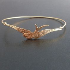 Sparrow Bracelet - A brass sparrow charm in an antique gold finish spreading his wings wide has been transformed into a delicate sparrow bangle bracelet with a gold tone brass band. The perfect gift for bird lovers.  I can also make this sparrow jewelry with a 14k gold filled band for an additional $10. If you would like this option for your sparrow bangle, select from options when ordering.  This sparrow bird bangle bracelet looks great in a stack together with others from my collection as…