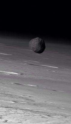 Phobos, the darkest moon in the solar system with the Martian terrain below by Mars Express.