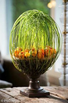 very arty egg shape arrangement of greens with orange flowers