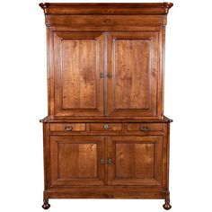 Very fine antique French Louis Philippe period buffet deux corps handcrafted of cherrywood by skilled artisans of Mont Saint-Michel, an island commune of in Normandy. This handsome piece accentuates the simple style that characterizes all Louis Philippe pieces, featuring a moulded doucine crown atop an upper cabinet sitting above a lower buffet fitted with three drawers over two doors. Resting on baluster feet.  This large buffet deux corps is less ornate than previous French styles, but is…
