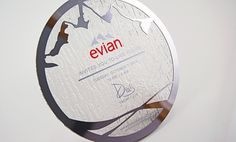 A water-textured acrylic invitation for Evian. A silver laser cut chrome frame emulates the brands' mountaintop logo.