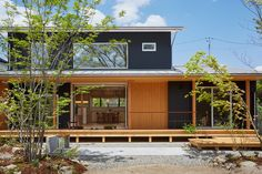 すっきりとした黒色のガルバリウムに、 緑豊かな木々と大きなウッドデッキが特徴的な外観のお家。 南側に大きく開いた窓から心地よい風と景色を取り込む間取り。 軒の深いウッドデッキは暑い夏の日や雨の日も庭を愉しむことができます。 道路側にも木々を配置し、自然に周囲の視線をカットしています。 リビングと和室は、吹き抜けごしにゆるやかにつながる、広々とした空間です。