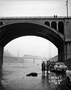 A pair of onlookers on the Broadway Bridge watch as coroners and a detective keep vigil over a man's body in the Los Angeles River bed, 1955. Photograph by R. Rittenhouse. © Los Angeles Police Department. Courtesy fototeka.