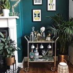 A vintage drinks trolley turned into a gin bar! Dark green walls and green prints in the corner of this living room #barcartstyling #barcart #ginstagram #ginbar #livingroomdecor #livingroomdesign #melaniejadedesign