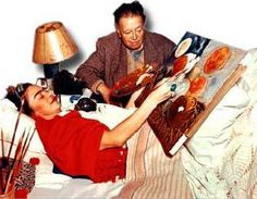 Frida Kahlo painting under the watchful eye of Diego Rivera.