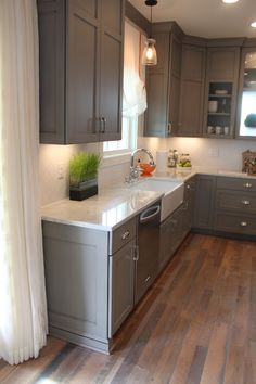 Gray kitchen cabinets, white counter top, wood floors