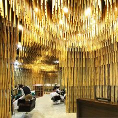 Thousands of bamboo rods hang from the ceiling like stalactites to divide the space inside this Bangkok hair salon.