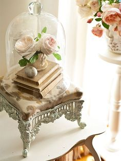 •Footstools   Repurpose a Victorian footstool as a stand for highlighting books and flowers. Cream-color paint and a modern ikat fabric refreshed this eBay find. A glass cloche elegantly crowns the book and floral arrangement sitting on top of the stool.