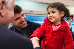 John McCallum, left, Minister of Immigration, Refugees and Citizenship, meets two-year-old Syrian refugee Minisa, right, and her father Yousef, centre, at Pearson International Airport in Toronto on Monday, February 29, 2016.