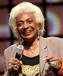 Nichelle Nichols (née Grace Dell Nichols on December 28, 1932) is an American actress, singer and voice artist. She sang with Duke Ellington and Lionel Hampton before turning to acting. Nichols' most famous role is that of communications officer Lt. Uhura aboard the USS Enterprise in the popular Star Trek TV series (1966-1969), as well as the succeeding motion pictures, where her character was eventually promoted in Starfleet to the rank of commander.