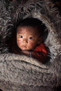 Tibetan baby in yak fur! Photo by Alison Wright ♥www, jsimens-helping families worldwide